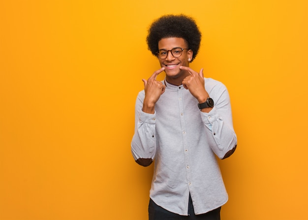 Jeune homme afro-américain sur un mur orange sourit, pointant la bouche