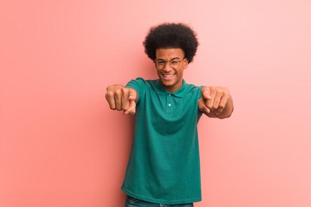 Jeune homme afro-américain sur un mur rose gai et souriant pointant vers l'avant