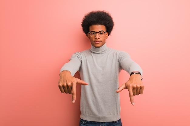 Jeune homme afro-américain sur un mur rose pointant vers le bas avec les doigts