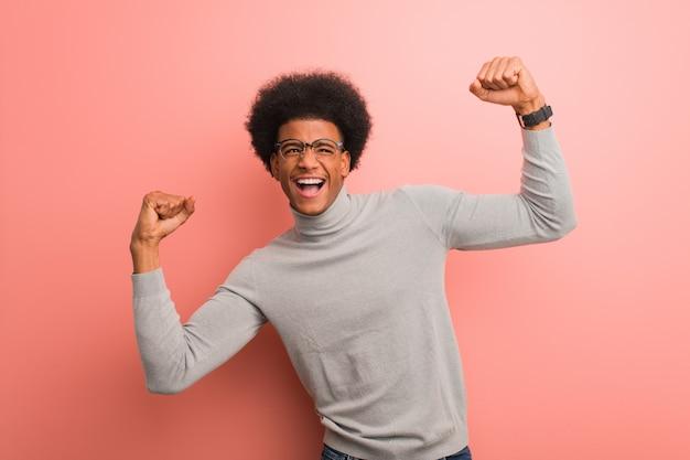 Jeune homme afro-américain sur un mur rose qui ne se rend pas