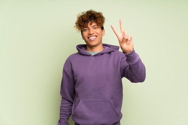 Jeune homme afro-américain sur le mur vert isolé, souriant et montrant le signe de la victoire
