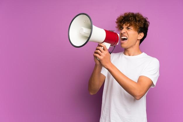 Jeune homme afro-américain sur mur violet isolé criant à travers un mégaphone