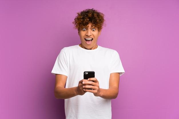 Jeune homme afro-américain sur mur violet isolé surpris et envoyant un message