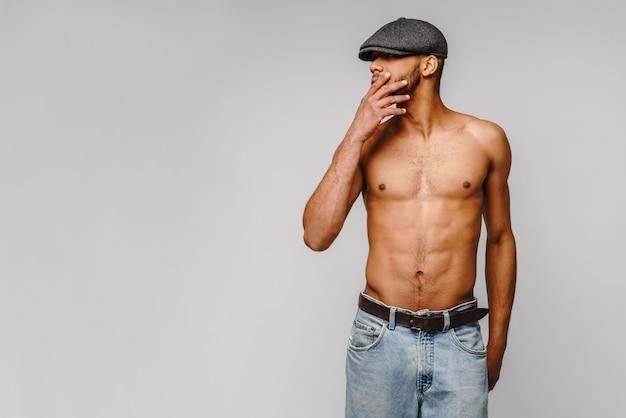 Jeune homme afro-américain musclé torse nu portant une casquette sur un mur gris clair
