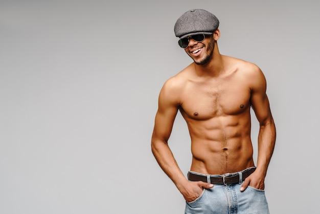 Jeune homme afro-américain musclé torse nu portant des lunettes de soleil et une casquette sur un mur gris clair