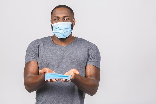 Jeune homme afro-américain noir en offrant un masque stérile isolé sur fond blanc.