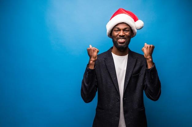 Jeune homme afro-américain portant bonnet de noël de noël très heureux et excité faisant le geste gagnant avec les bras levés, souriant et criant pour le succès.