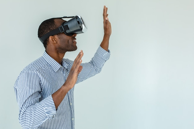 Jeune homme afro-américain portant un casque de réalité virtuelle vr sur mur blanc