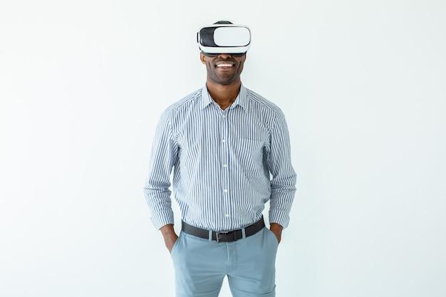 Jeune homme afro-américain portant un casque vr en se tenant debout contre le mur blanc