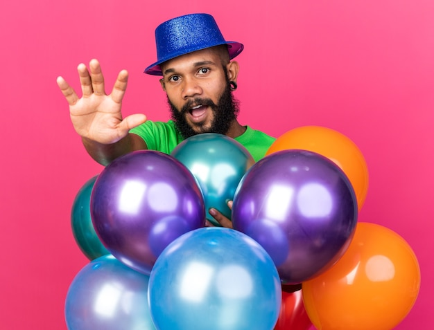 Jeune homme afro-américain portant un chapeau de fête debout derrière des ballons isolés sur un mur rose