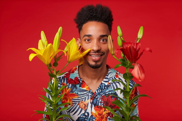Jeune homme afro-américain, porte en chemise hawaïenne, regarde la caméra avec une expression heureuse, se dresse sur fond rouge avec des fleurs jaunes et rouges et des sourires.