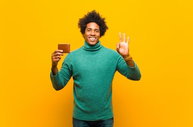 Jeune homme afro-américain avec un portefeuille contre l'orange