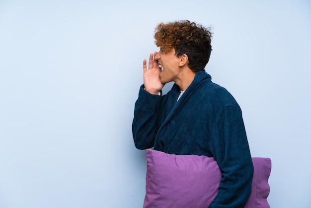 Jeune homme afro-américain en pyjama criant avec la bouche grande ouverte