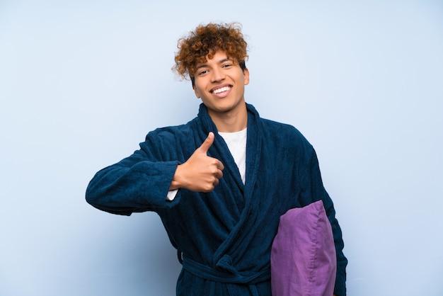 Jeune homme afro-américain en pyjama donnant un geste du pouce levé