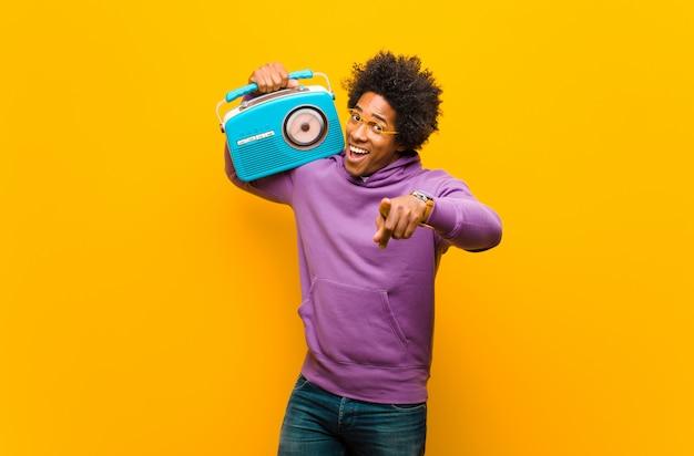 Jeune homme afro-américain avec une radio vintage orange b