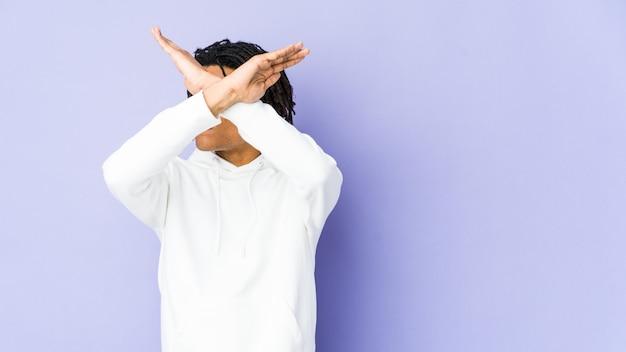 Jeune homme afro-américain rasta gardant deux bras croisés, concept de déni.