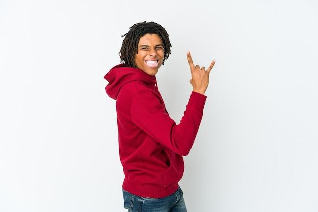 Jeune homme afro-américain rasta montrant le geste de la roche avec les doigts