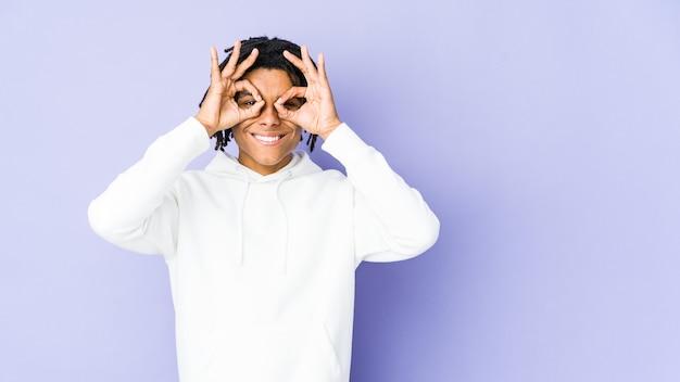 Jeune homme afro-américain rasta montrant un signe correct sur les yeux