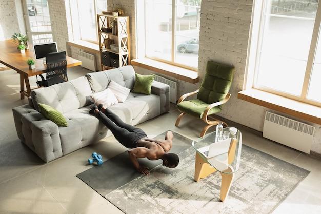 Jeune homme afro-américain s'entraînant à la maison, faisant des exercices de fitness, aérobie.