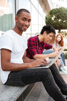 Jeune homme afro-américain souriant assis avec ses amis et utilisant un ordinateur portable à l'extérieur
