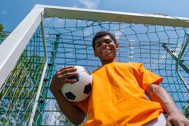 Jeune homme afro-américain souriant tenant un ballon de football en se tenant debout dans un but de football sur un terrain de sport à l'extérieur en été, vue de dessous