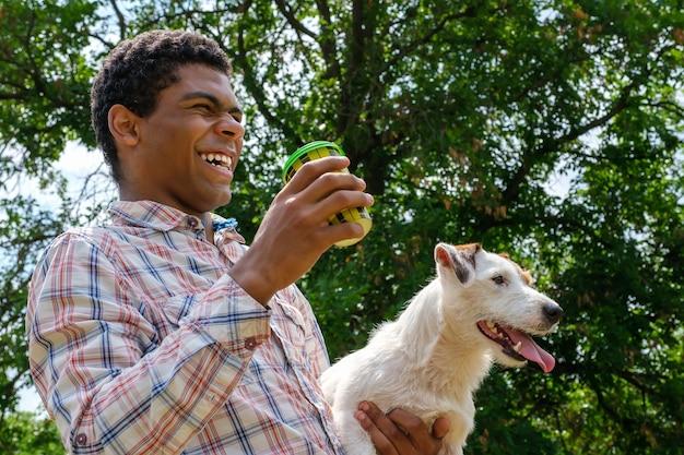 Jeune homme afro-américain souriant tenant un chien terrier jack russell et un café à emporter. balade dans le parc en été, low angle view