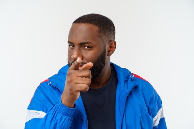 Jeune homme afro-américain de sport avec un doigt pointé avec surprise, se sent prospère et prospère