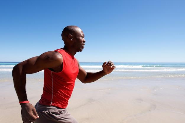 Jeune homme afro-américain sprint sur la plage