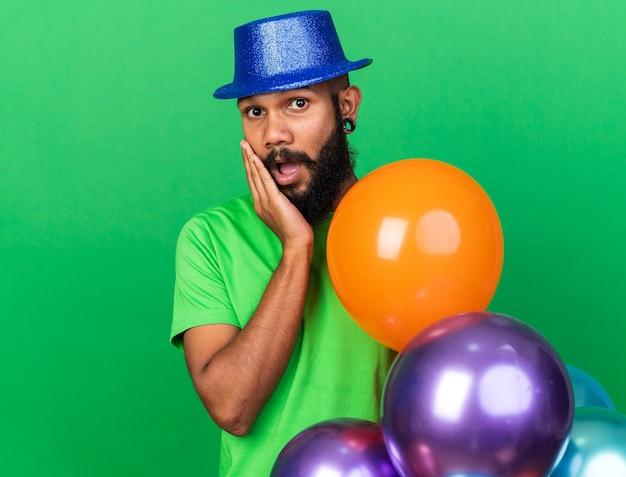 Jeune homme afro-américain surpris portant un chapeau de fête mettant la main sur la joue