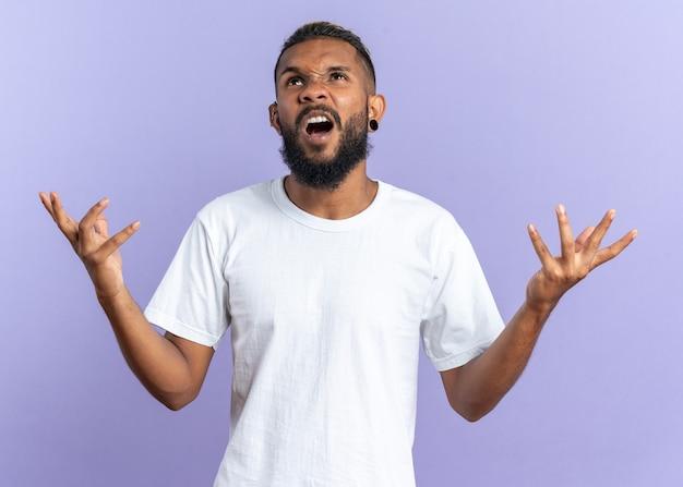 Jeune homme afro-américain en t-shirt blanc criant d'être frustré avec les bras levés debout sur bleu