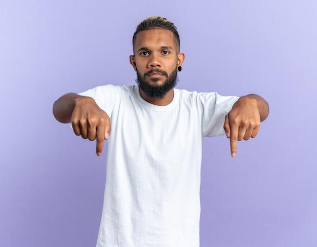 Jeune homme afro-américain en t-shirt blanc regardant la caméra avec un visage sérieux pointant