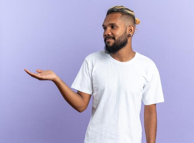 Jeune homme afro-américain en t-shirt blanc regardant de côté avec le bras tendu présentant un espace de copie souriant debout sur fond bleu