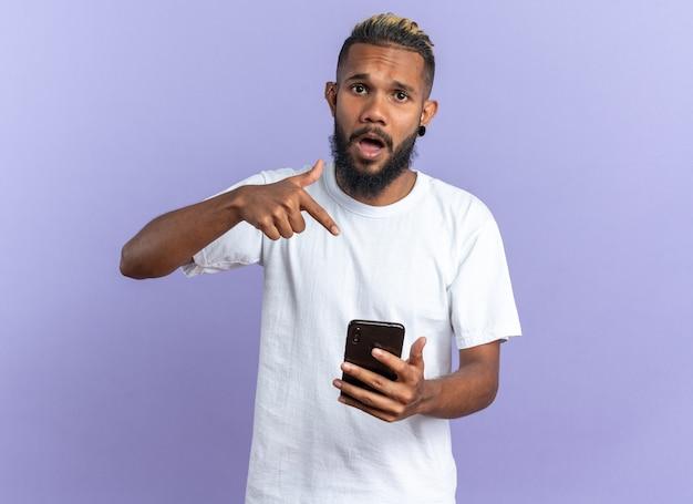 Jeune homme afro-américain en t-shirt blanc tenant un smartphone pointant
