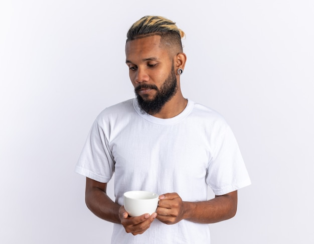 Jeune homme afro-américain en t-shirt blanc tenant une tasse de thé chaud regardant de côté avec une expression triste