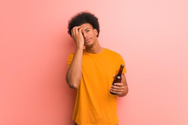 Jeune homme afro-américain tenant une bière inquiet et débordé