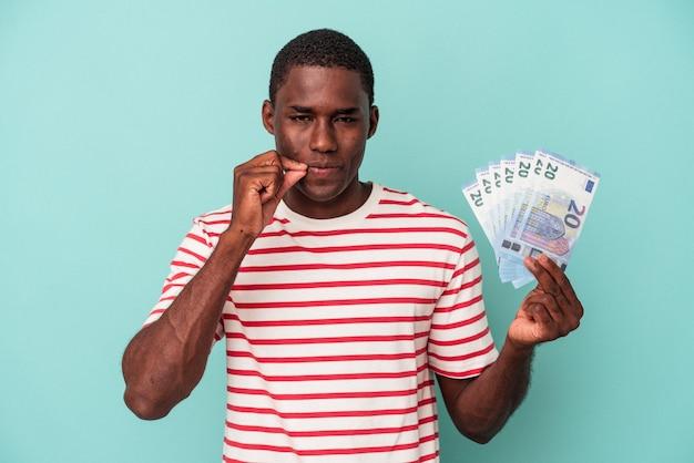 Jeune homme afro-américain tenant un billet de banque isolé sur fond bleu avec les doigts sur les lèvres gardant un secret.