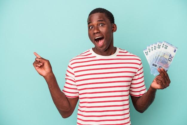 Jeune homme afro-américain tenant un billet de banque isolé sur fond bleu pointant vers le côté