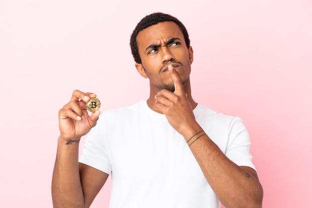 Jeune homme afro-américain tenant un bitcoin sur fond rose isolé ayant des doutes tout en levant