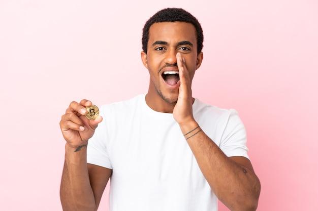 Jeune homme afro-américain tenant un bitcoin sur fond rose isolé criant avec la bouche grande ouverte