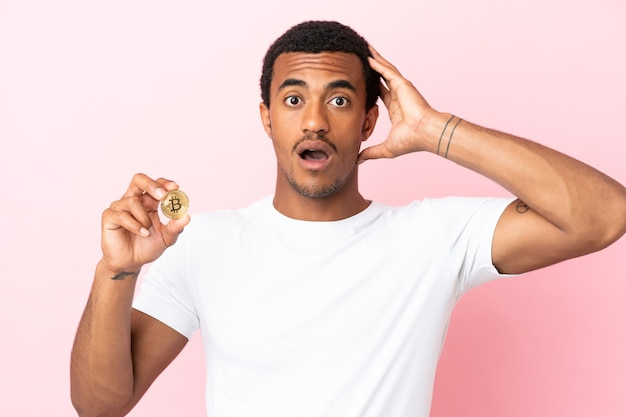 Jeune homme afro-américain tenant un bitcoin sur fond rose isolé avec une expression de surprise