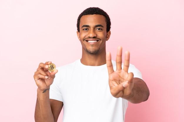 Jeune homme afro-américain tenant un bitcoin sur fond rose isolé heureux et comptant trois avec les doigts