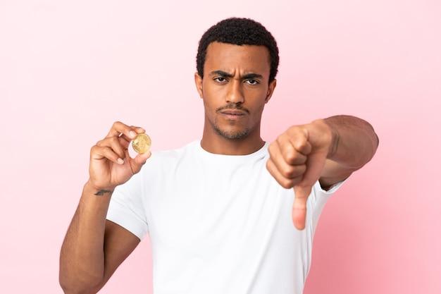 Jeune homme afro-américain tenant un bitcoin sur fond rose isolé montrant le pouce vers le bas avec une expression négative