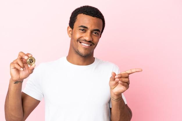 Jeune homme afro-américain tenant un bitcoin sur fond rose isolé, pointant le doigt sur le côté