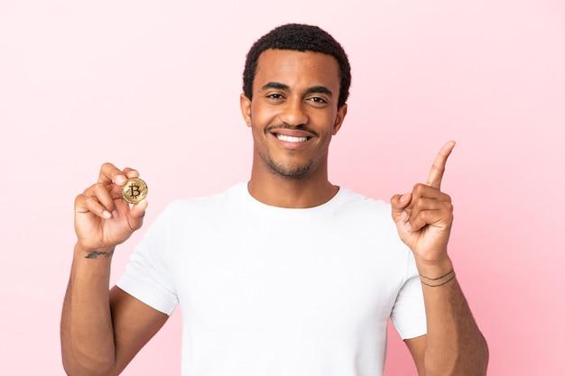 Jeune homme afro-américain tenant un bitcoin sur fond rose isolé pointant vers une excellente idée