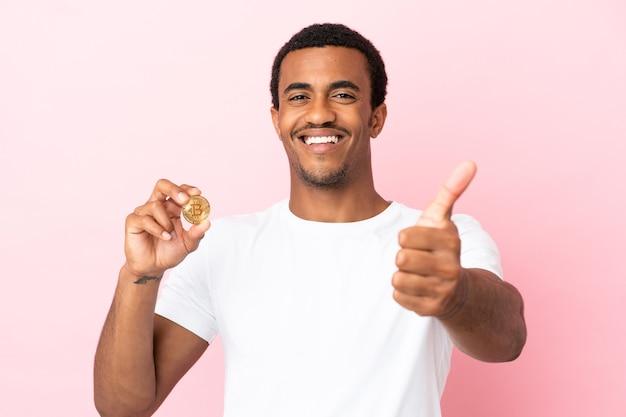 Jeune homme afro-américain tenant un bitcoin sur fond rose isolé avec le pouce levé parce que quelque chose de bien s'est produit