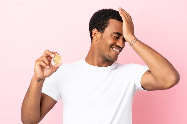 Un jeune homme afro-américain tenant un bitcoin sur fond rose isolé a réalisé quelque chose et envisage la solution
