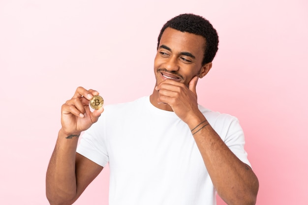Jeune homme afro-américain tenant un bitcoin sur fond rose isolé regardant sur le côté et souriant