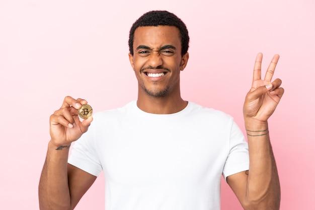 Jeune homme afro-américain tenant un bitcoin sur fond rose isolé souriant et montrant le signe de la victoire