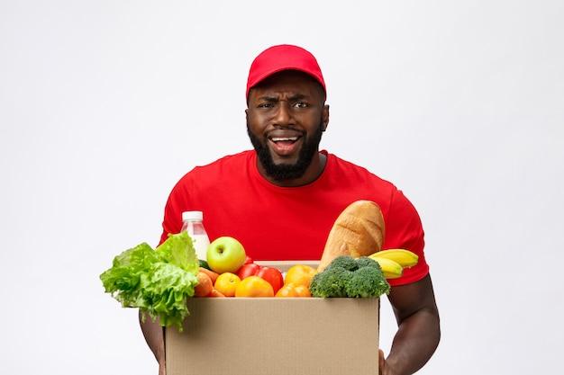 Jeune homme afro-américain tenant la boîte d'épicerie dans les mains avec un visage choquant.