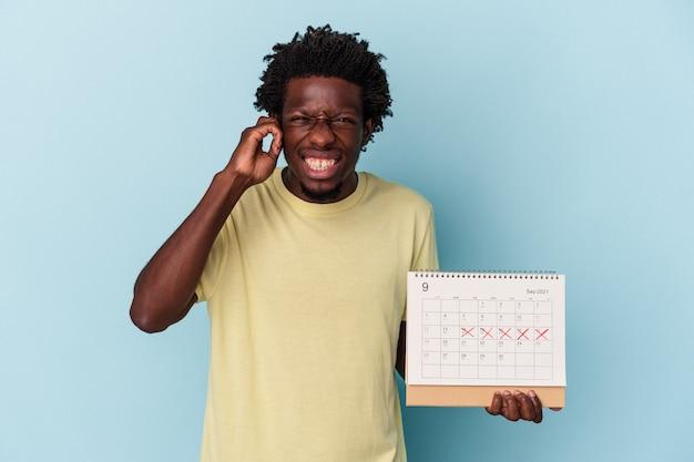 Jeune homme afro-américain tenant un calendrier isolé sur fond bleu couvrant les oreilles avec les mains.